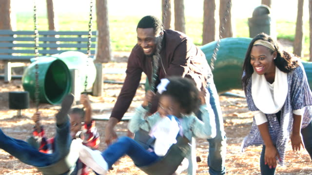 African-American family playing on playground swing