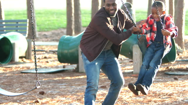 African-American father and son on playground swing An African-American man in his 30s playing with his 7 year old son on the playground. The little boy is sitting on a swing and his father is pushing him. swinging stock videos & royalty-free footage