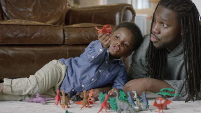 afro-amerikansk far och son leker med leksaker i deras vardagsrum - föreställningsförmåga bildbanksvideor och videomaterial från bakom kulisserna