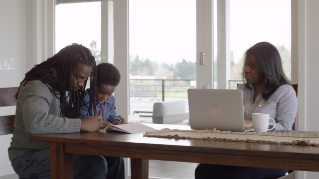 vídeos y material grabado en eventos de stock de colores de padre afroamericano con su hijo mientras su esposa trabaja en un portátil - trabajo desde casa