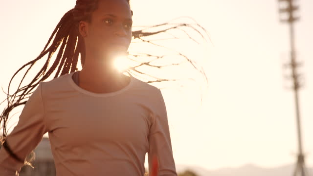 SLO MO DS African-American female athlete running in the sunny stadium at sunset