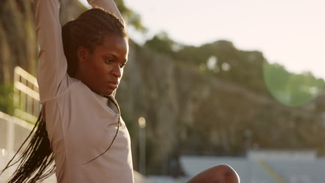 SLO MO African-American female athlete stretching in the stadium on the track in setting sun