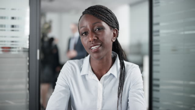 African-American female employee on a video call from the office Medium locked down shot of an African-American female employee on a video call from her office. Shot in Slovenia. businesswear stock videos & royalty-free footage