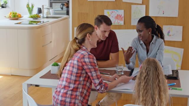 afro-amerikanska kvinnliga försäkringsagent ha ett möte med en familj hemma - 20 sekunder eller längre bildbanksvideor och videomaterial från bakom kulisserna