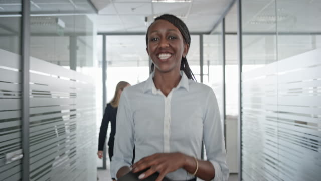 African-American female office employee smiling as she walks down the office hallway Wide handheld shot of a smiling African-American woman looking into the camera while walking down the hallway before entering her office. Shot in Slovenia. bolos stock videos & royalty-free footage