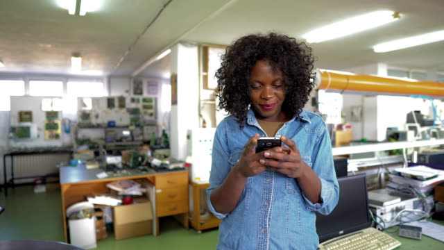 African-American female worker using cell phone in engineering office