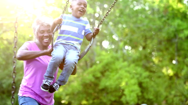 african-american grandmother pushing boy on swing - aktywni seniorzy filmów i materiałów b-roll
