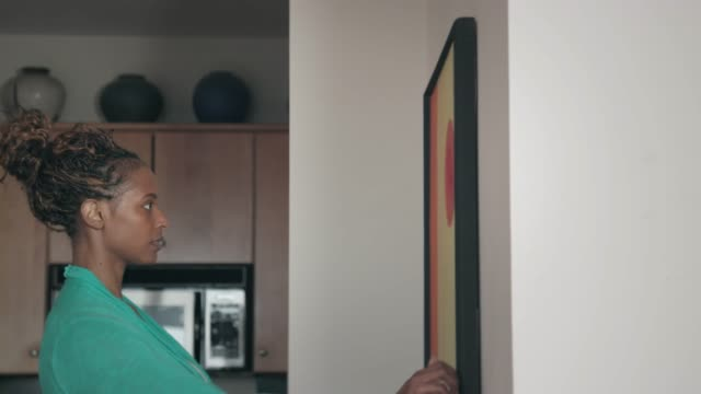 vídeos de stock e filmes b-roll de african-american hanging framed art - bricolage