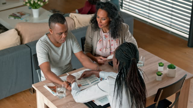 african-american insurance agent advising a multi ethnic couple in their home - insurance filmów i materiałów b-roll