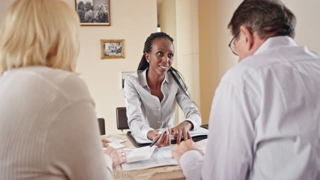 African-American insurance agent advising couple in their home