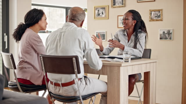 African-American insurance agent consulting a senior couple in their home video