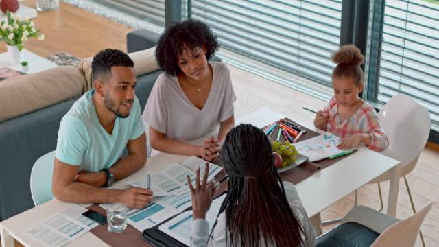 vídeos de stock e filmes b-roll de african-american insurance agent talking to a multi ethnic couple at their home - cabelo preto