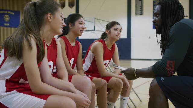 vidéos et rushes de afro-américaine entraîneur masculin discutant un jeu avec l'équipe de basket-ball filles - 18 19 ans