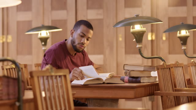 LD African-American male student reading in the library video