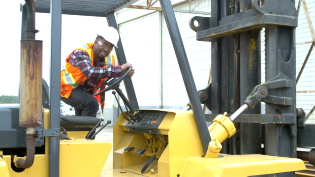African-American man climbs onto forklift