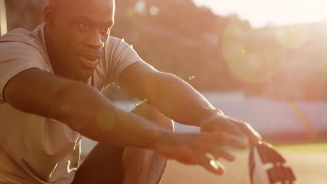 SLO MO africano-americano hombre haciendo estiramientos ejercicios en el estadio al atardecer - vídeo