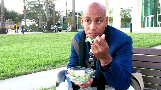 African-American man eating take out food