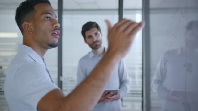 African-American man explaining a graph on the screen in meeting room to his male Caucasian colleague