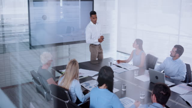 african-american man giving a presentation to his colleagues in conference room - emozione positiva video stock e b–roll