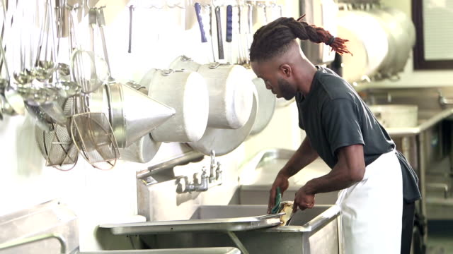 african-american man in commercial kitchen washing pots - struttura pubblica video stock e b–roll