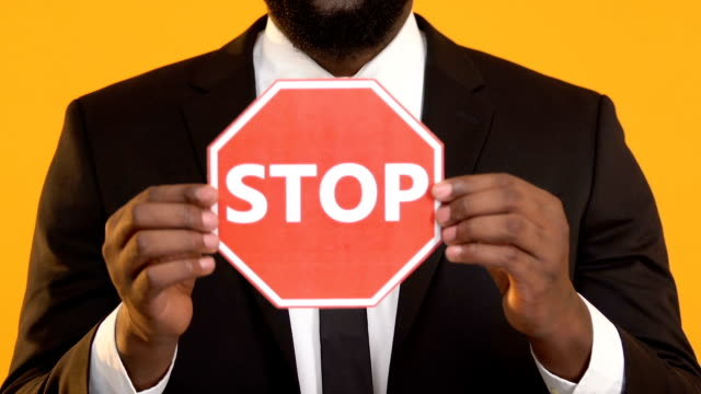 African-American man in suit showing stop sign into camera, work racism protest African-American man in suit showing stop sign into camera, work racism protest civil rights stock videos & royalty-free footage