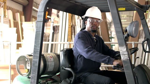 African-American man in warehouse climbs onto forklift An African-American man working in a warehouse climbs onto a forklift, buckles his seat belt and then looks at the camera. forklift stock videos & royalty-free footage