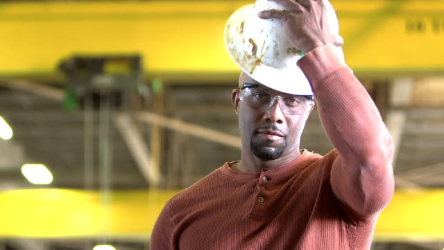 African-American man in warehouse puts on hardhat A tough-looking, African American man staring at the camera. He is a worker standing in a warehouse wearing safety glasses. He puts on a hardhat and smiles. work helmet stock videos & royalty-free footage
