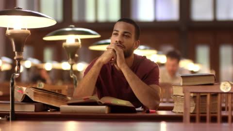 vídeos y material grabado en eventos de stock de ds african-american man pondering de la biblioteca - estudiante