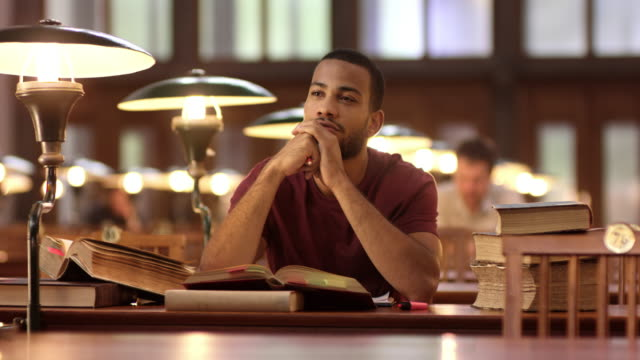 DS African-American man pondering in the library Medium dolly shot of a young African-American man pondering behind a desk full of books in the library's reading room. adult stock videos & royalty-free footage