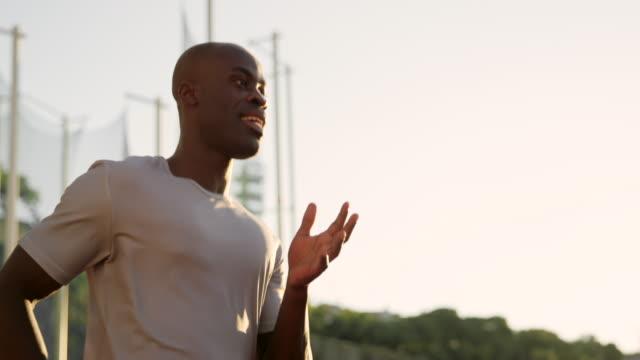 vidéos et rushes de slo mo ts tu afro-américaine homme qui court dans le stade au coucher du soleil - athlétisme
