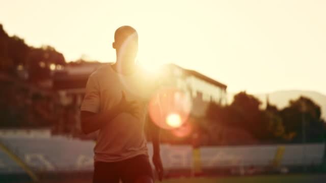 SLO MO DS africano-americano hombre corriendo en el estadio de puesta de sol con las llamaradas - vídeo