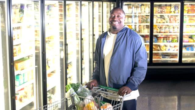 afroamerikanischer mann beim einkaufen für lebensmittel - gefrierkost stock-videos und b-roll-filmmaterial