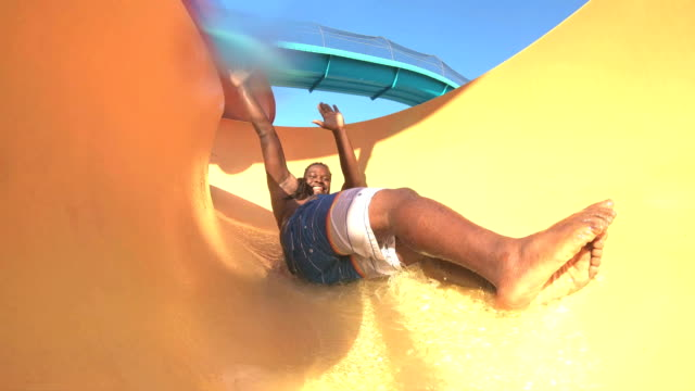 african-american man sliding down water slide - scivolo video stock e b–roll