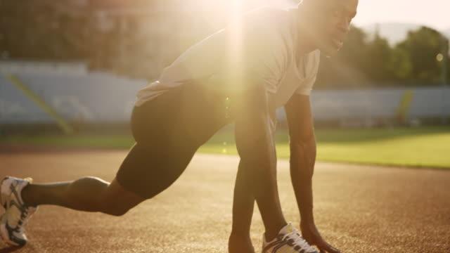 SLO MO africano-americano hombre estirando en el estadio de la pista en la puesta del sol - vídeo