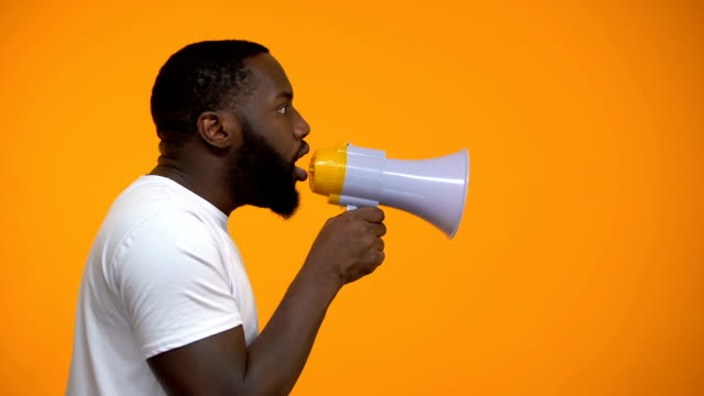 African-American man using megaphone for protest, calling to action, side view African-American man using megaphone for protest, calling to action, side view announcement message stock videos & royalty-free footage