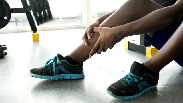 vídeos de stock, filmes e b-roll de homem afro-americano com crick sentada no chão e massageando sua perna - perna termo anatômico