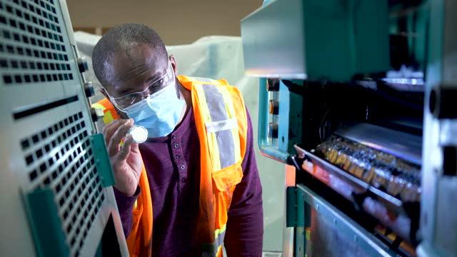 vídeos de stock e filmes b-roll de african-american man with mask  inspecting printing press - lanterna elétrica
