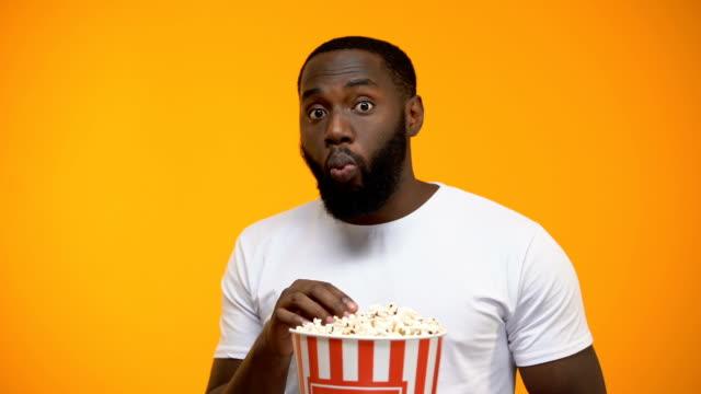 stockvideo's en b-roll-footage met afro-amerikaanse man met popcorn aandachtig kijken naar interessante tv programma - popcorn