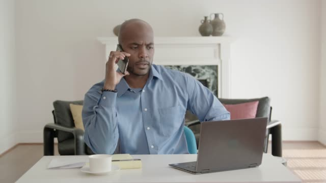African-American Man Working from Home Office and Talking on his Mobile Phone video