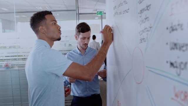 afroamerikansk man skriva ett diagram på en whiteboard och hans manliga kollega hjälper honom - whiteboardtavla bildbanksvideor och videomaterial från bakom kulisserna