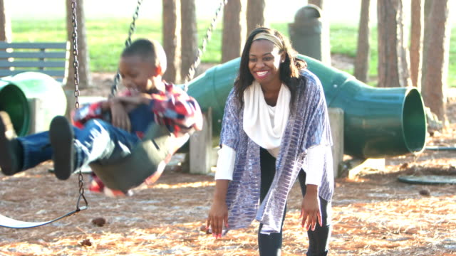 African-American mother and son on playground swing A young African-American woman in her 20s playing with her 7 year old son on the playground. The little boy is sitting on a swing and his mother is pushing him. swinging stock videos & royalty-free footage