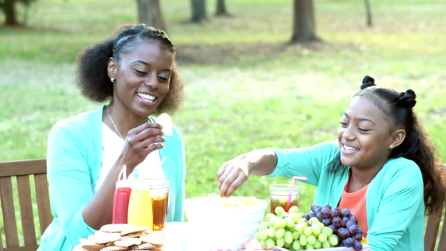 African-American mother, daughter, having fun at cookout An African-American mother and her 10 year old daughter having fun together at a backyard cookout. They are sitting at a table eating potato chips, laughing. potato chip stock videos & royalty-free footage
