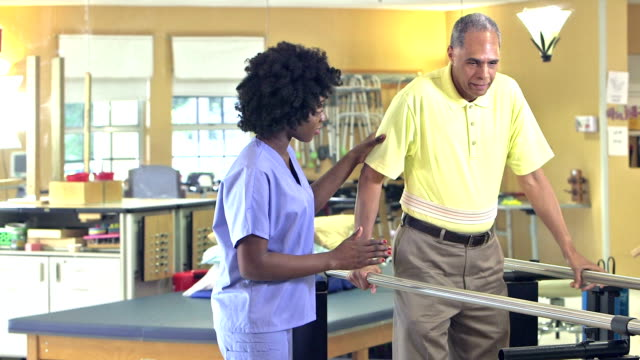 african-american physical therapist helping patient - fisioterapia video stock e b–roll