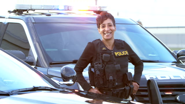 African-American policewoman standing by patrol car