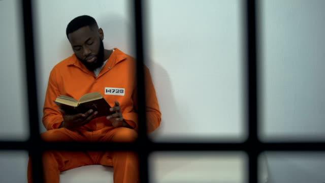 聖書、有罪判決を受けた罪人、宗教を読むアフリカ系アメリカ人の囚人 - 犯罪者点の映像素材/bロール
