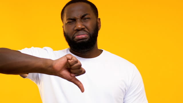 African-American showing disgust at bad smell and thumbs down, poor quality food