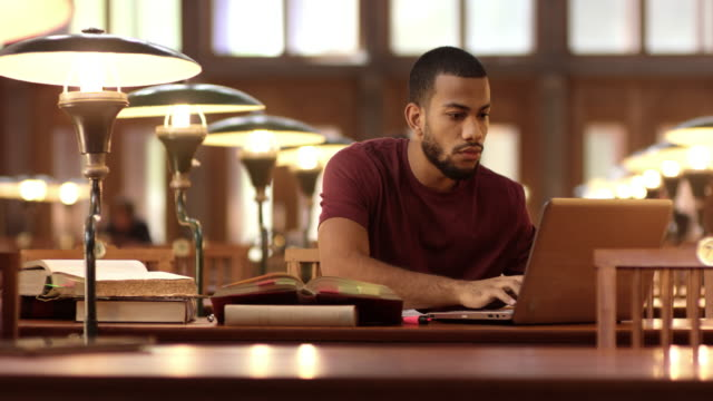 DS African-American student studying in the library with a laptop video