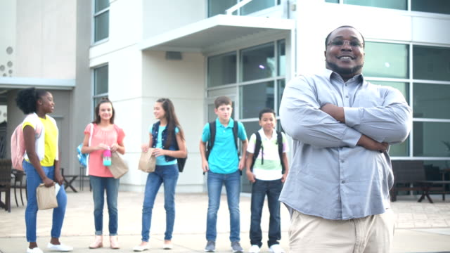 African-American teacher or parent outside middle school An African-American teacher or parent standing outdoors in front of a school building, middle school students out of focus behind him. He is a mature man in his 40s, smiling at the camera with his arms crossed. middle school teacher stock videos & royalty-free footage