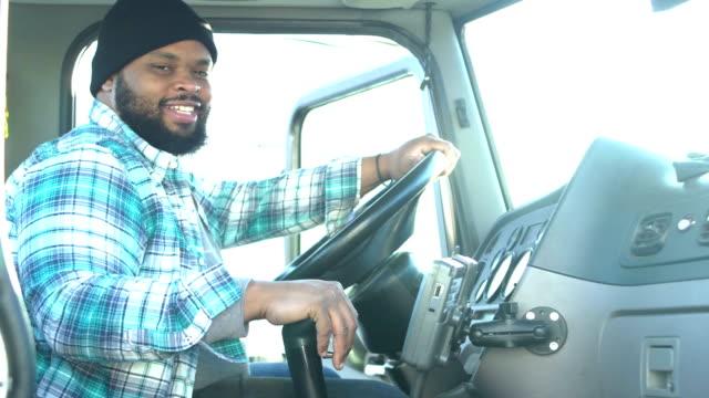vídeos y material grabado en eventos de stock de camionero afroamericano en el asiento del conductor del semi-camión - conductor de autobús