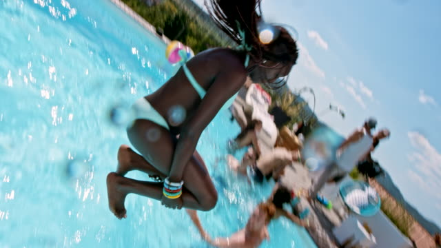 SLO MO African-American woman and a Caucasian man jumping into the pool at the party one after another Slow motion wide handheld shot of an  African-American woman jumping into the pool at the pool party followed by her male Caucasian friend doing a summersault into the pool. Shot in Slovenia. pool party stock videos & royalty-free footage